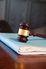 Shows picture of a judge's gavel on top of a file folder with many papers.