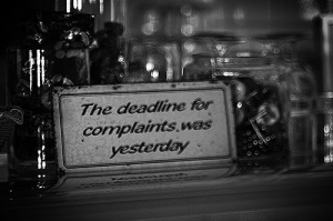 Black and white photo shows an old looking sign that says, The deadline for complaints was yesterday.