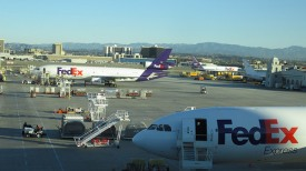 Picture shows two FedEx planes on an airport runway.