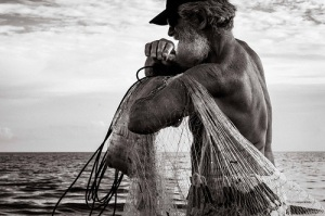 Older man in a boat on the water pulling up a fishing net.