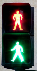 Stop sign shows a person light in green and a person lit in red.