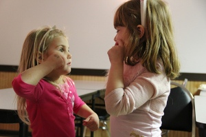 Two girls use sign language with one another.