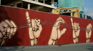 Street painting of sign language hand showing beginning of alphabet, A, B, C, D...