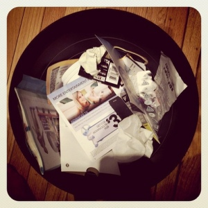 Picture of a wastebasket with balls of paper trash inside.