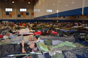 Gym with hundreds of people laying on the floor in sleeping bags.