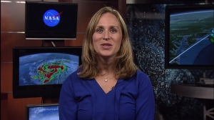Female news broadcaster with image of Hurricane Matthew in the background.