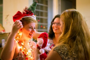 The women communicate in bright lightning. One is wearing a string of lights and a Santa hat.