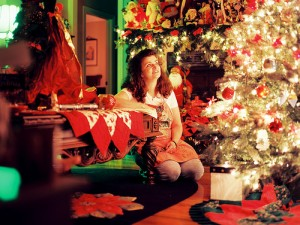 Woman sits on floor in front of a bright Christmas tree.