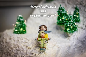 One child statue holds another in the snow. Words read Merry Christmas and Happy New Year!