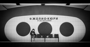Black and white picture: girl sits alone under a sign that is probably in Russian.