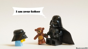 "Darth Vader Lego figure holds a teddy bear and says to a shorter Darth Vader kid figure, ""I am your father."""