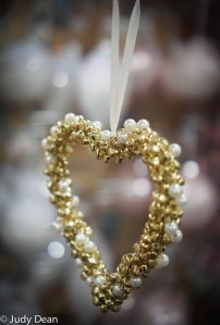 Gold and pearl heart ornament hangs on a Christmas tree with white lights in background.