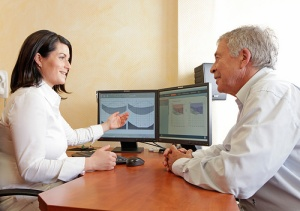 Woman sits in front of a computer with a chart showing a hearing range for a man sitting at her desk.