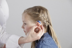 Adult puts a blue hearing aid on a young girl.