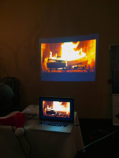 Computer screen and projected image of a crackling fireplace fire.