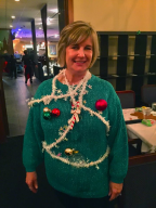 Sign Shares' Kathy Fritsche wears a green sweater with attached ornaments and tinsel.
