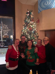 Men and women in holiday sweaters pose in front of a lit Christmas tree inside a restaurant.