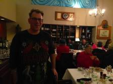 Man walks toward camera smiling while people dressed in holiday reds talk and eat behind him.