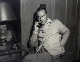 Black and white picture of a young Bob Hope on the telephone.