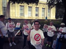 Picture of people with T-shirts and signs that protest Video Remote Interpreters.