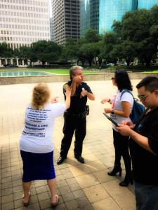 A police officer and a woman use sign language, while others take notes.