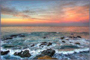 Picture of sunset with waves skimming over rocks in the water.