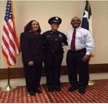 Two people in business attire stand with their daughter, wearing a police uniform.