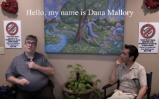 Two men sit, one signs, Hello, my name is Dana Mallory.