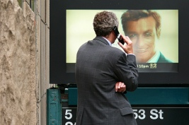 Man talks on cell phone looking at big picture of a man.