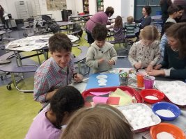 Adults and small children make paper crafts in classroom.