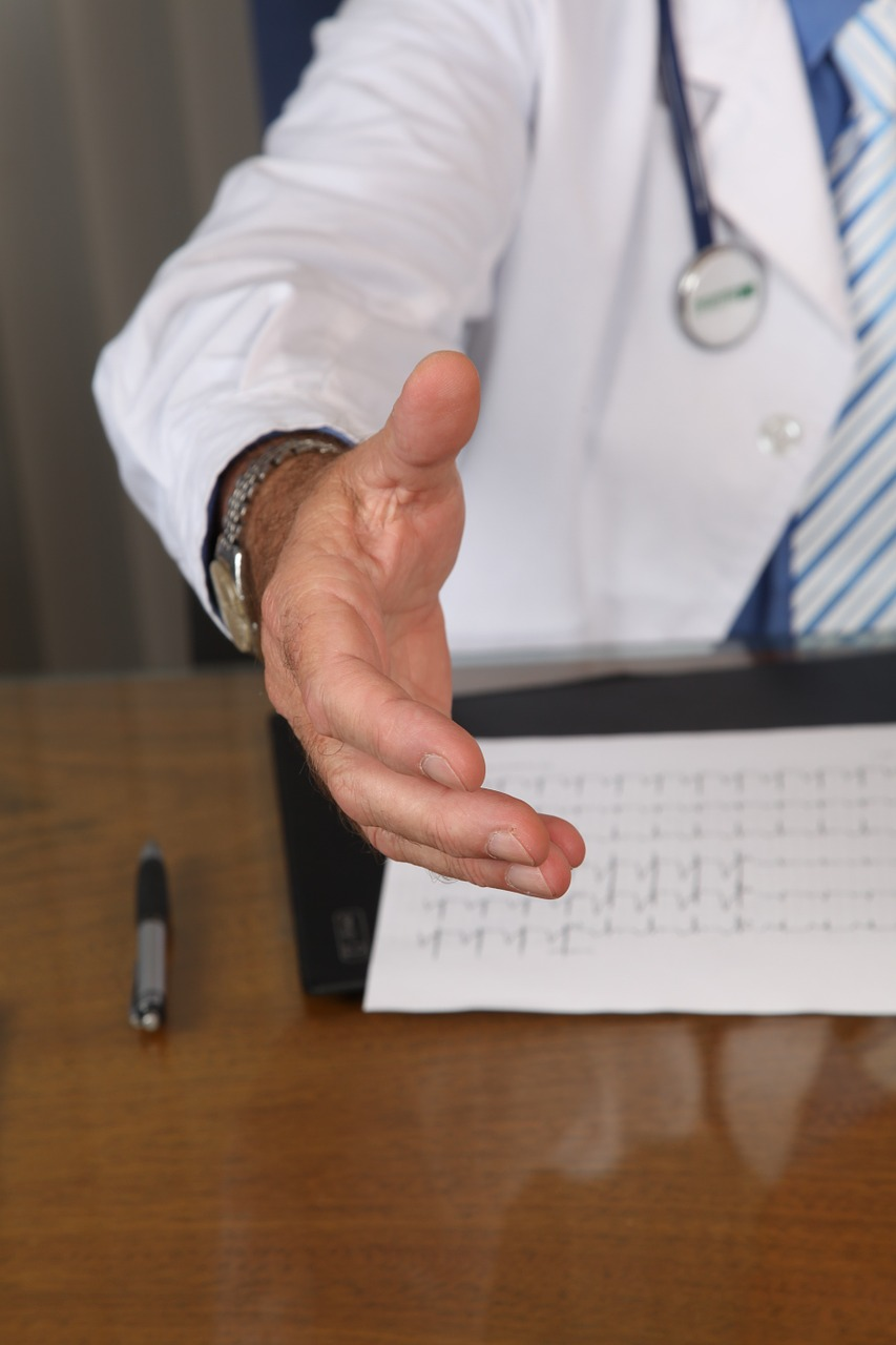 sign shares inc news sharing our communites in each doctor sitting at desk reaches out hand for a handshake