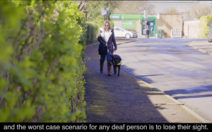 "Young woman walks down street using a guide dog. Words at bottom of slide ""and the worst case scenario for any deaf person is to lose their sight"""