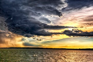 Color-enhanced picture of clouds over the ocean, showing golden and pink hues against black storm clouds.