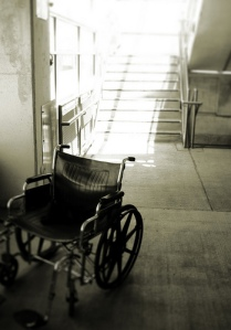 Black and white photo of an empty wheelchair at the bottom of some stairs.