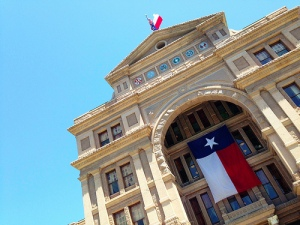 A picture of a Texas Capitol entrance with the Texas flag hanging in front and on top of the Capitol.